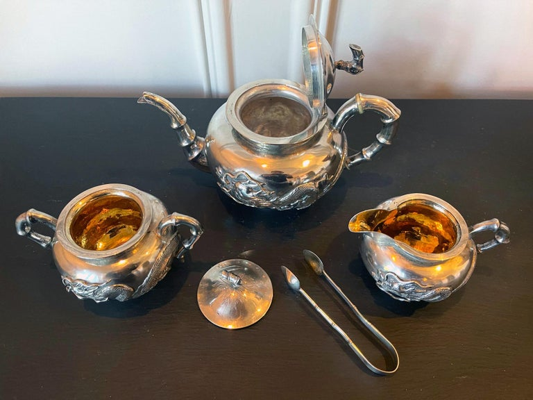 A four piece Chinese export silver tea service set consists of a lidded teapot, a creamer with lid, an open sugar and a tongs. The set was retailed by Zee Wo, a silver retailer located in Shanghai at 121 and 370 Henan Road and operated circa
