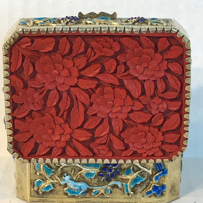 Chinese export silver vermeil enamel cinnabar box, of rectangular form with cross cut corners, exquisite highly detailed carved cinnabar floral reliefs, the box of silver, with gold wash and turquoise enamel work. The interior with a mirrored lid,