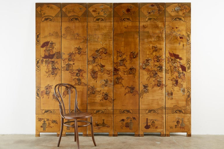 Fascinating Qing style Chinese export six-panel coromandel screen featuring a lacquer painted battle scene on a dramatic gilt background. The scene is bordered by a dragon motif and has decorative fans on the top of each panel and floral vases with