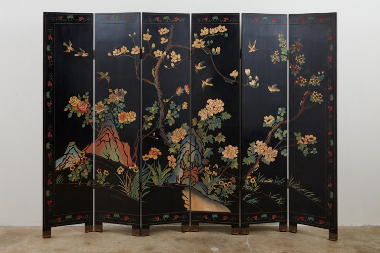 Colorful Chinese export six-panel Coromandel screen. Features a black lacquered ground decorated with a vibrant floral and foliate landscape. The stylized scene has colorful birds and is bordered with a red floral motif. Supported by small