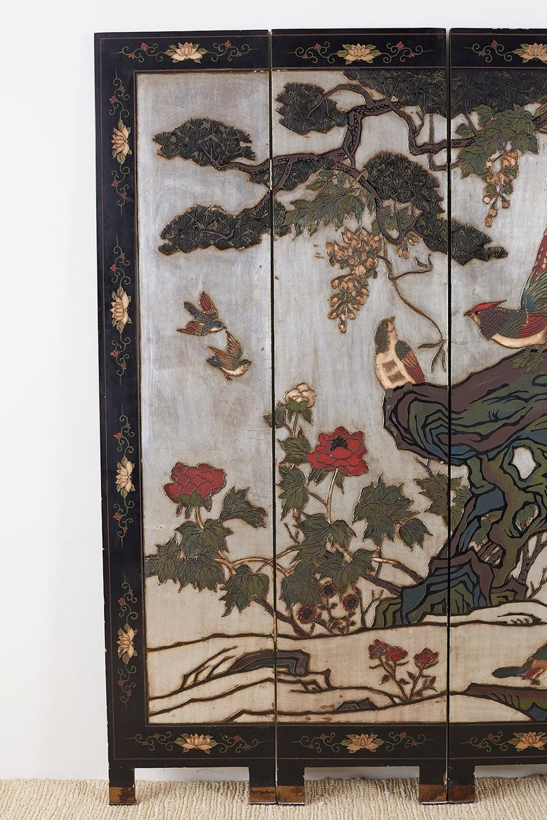 Impressive Chinese export six-panel folding coromandel screen depicting flora and fauna. Constructed from lacquered wooden panels hand carved and painted. Features a rare silver leaf background that make the scene Stand out with vibrant colors and