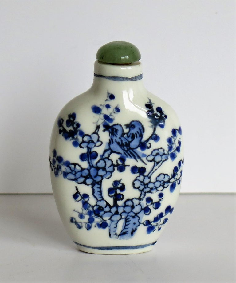 This is a good Chinese porcelain snuff bottle, hand painted in cobalt blue and with a very good hardwood stand, all circa 1940.  The bottle is hand painted over-glaze in shades of cobalt blue over a white glaze. The decoration shows two birds