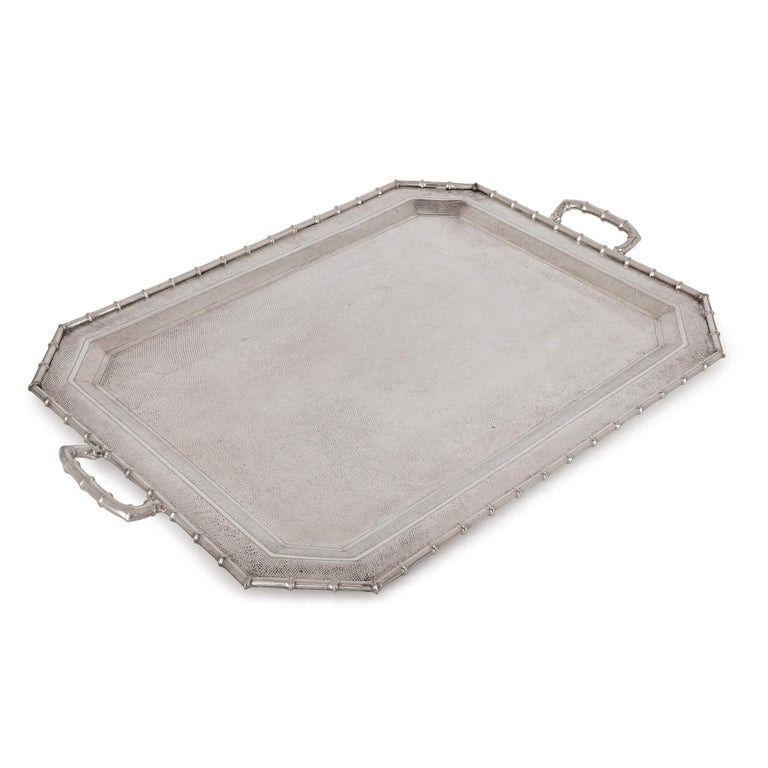 This silver tray is a beautiful piece of tableware, which skilfully blends Eastern and Western decorative styles. It has been decorated with a twisted bamboo edge, bamboo handles and the tray base has been carefully hammered to give the piece a