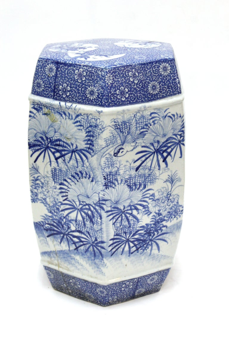 Chinese Export style garden stool in ceramic. The piece has a hexagonal shape and has decorative motifs in blue on white background depicting natural themes. In great vintage condition with age-appropriate wear and use.