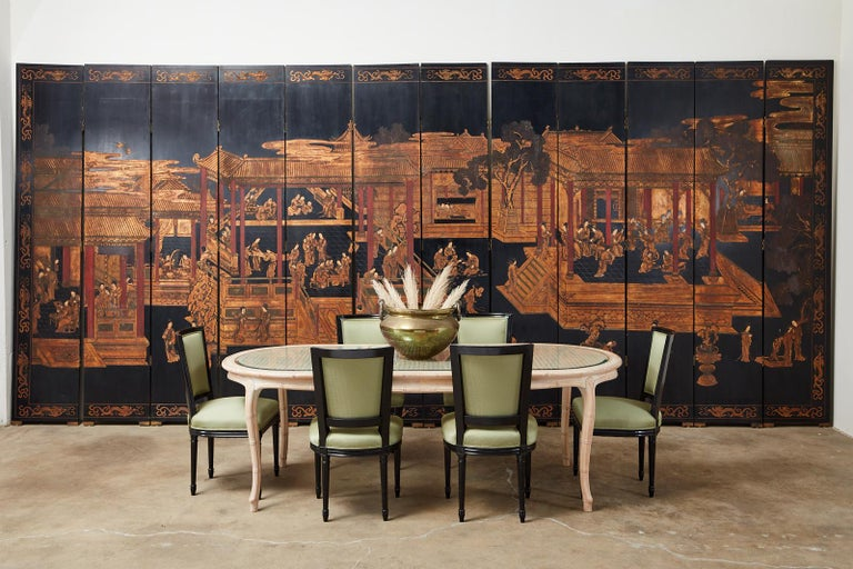 Grand scale Chinese export twelve-panel Coromandel screen featuring a pagoda garden pavilion with figures engaged in leisurely activities. The panels are intricately carved with thick layers of lacquer having a parcel gilt finish. Made on a large