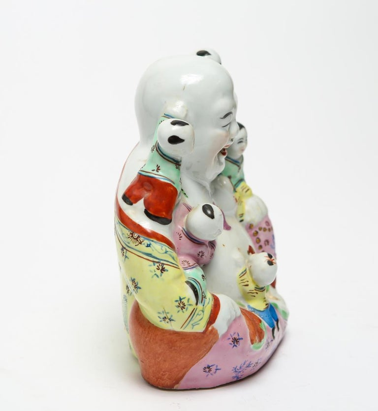 Chinese famille rose porcelain and poly-chrome enamel Hotei Laughing Buddha figure with five boys, probably dating from the Republic Era. The piece has an elaborately painted robe, the underside has a stamped maker's mark and impressed numbers.