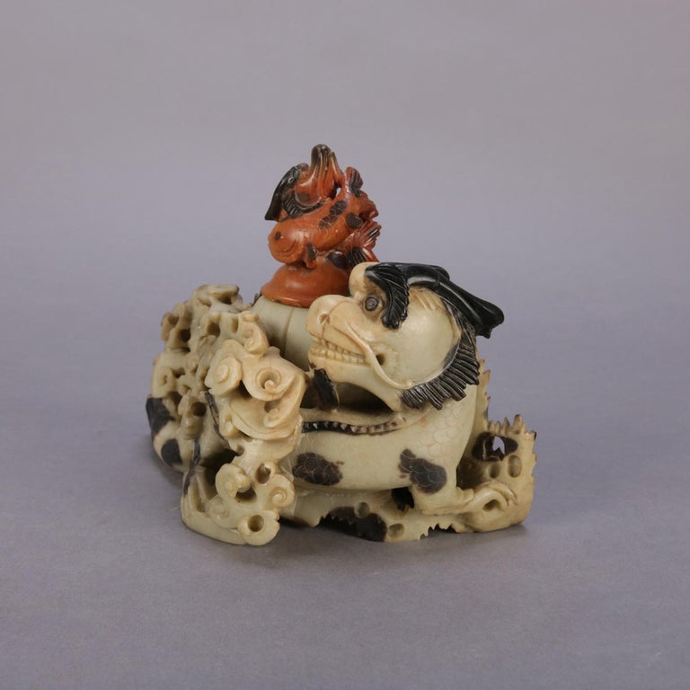 Antique figural Chinese carved soapstone sculptural inkwell features bi-colored dragon set in rolling sea waves and having carved top with koi (fish) finial, en verso dated with carved, 1900.