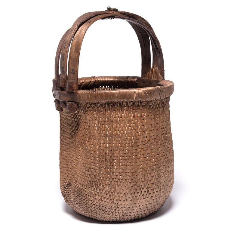 Basket making is an ancient and humble craft, but in the hands of a skilled weaver a simple willow basket becomes a truly beautiful statement. The artisan's mastery is evident in this early 20th century bent handle basket: the strong, flexible