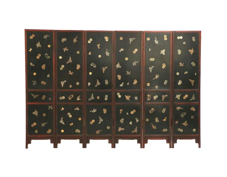 A six panel hinged folding floor screen from China circa end of the 19th- early 20th century. Constructed in a rosewood family hardwood likely Hong Mu. Each panel features three sections of black lacquered panels inlaid with a variety of objects