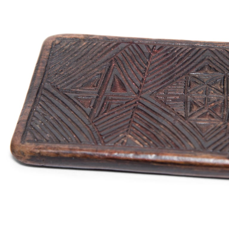 Dated to the 19th century, this flat wooden panel is curiously etched with geometric patterns and dense triangle-work. Its original use remains unknown, perhaps it was a divination tool, a traveling game board, or a weight to hold open a scroll. A