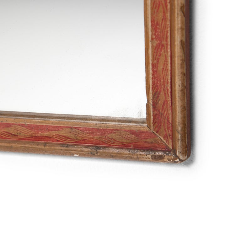 The painted frame of this wall mirror originally bordered a reverse glass painting, a traditional art that required the artist to paint an image in reverse, beginning with the details. Now enclosing a new mirror, the frame is painted with a