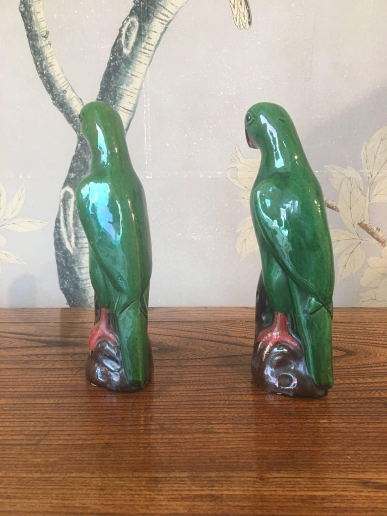 A pair of green early 20th century Chinese glazed parrots.