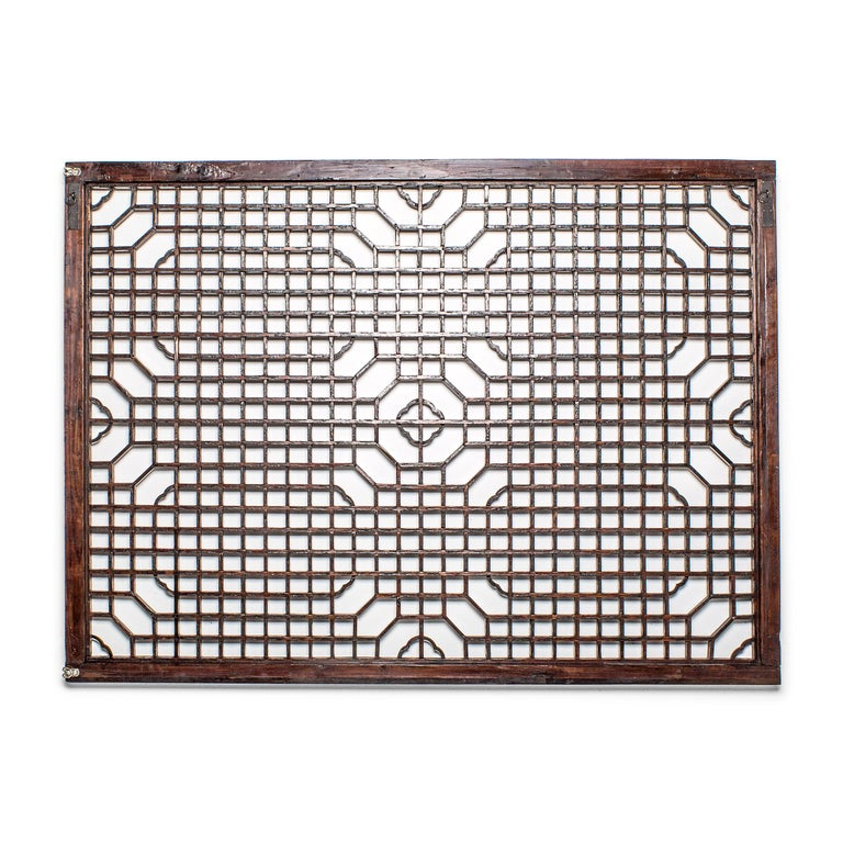 This lattice window panel likely originated in an aristocratic Chinese home with neutral and balanced interiors. The geometric lattice pattern is linear and open, and was designed originally to allow light and air into a room while maintaining