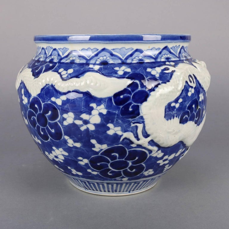 Chinese porcelain jardeniere features high relief dragon, hand painted allover floral decoration, collar with stylized tobacco leaf design, blue and white, 20th century
