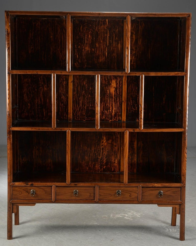 Chinese display cabinet or bookcase of stained hardwood, with compartments and drawers.