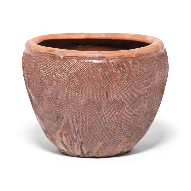 Once used to hold stockpiles of grain, this capacious terracotta jar is distinguished by the energetic incised pattern covering its exterior. Using a simple forked tool, the potter layered the vessel with dense etchings to enliven the simply shaped