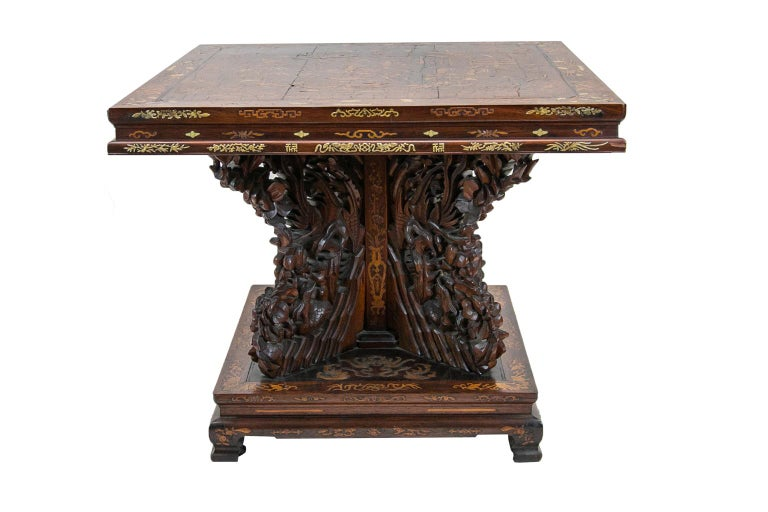 Chinese inlaid center table, is composed of rosewood and walnut. It is profusely inlaid with pagodas, human figures, birds, deer, water buffalo, and tree arabesques. It is inlaid with satinwood and bone. The legs on the base are in a cross