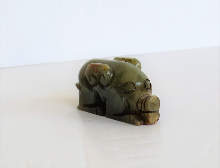 This is a Chinese natural jade, small hand carved stylized pig, possibly made as a talisman, which we date to the 19th century, Qing period.  This piece is made from natural Jade stone that is mainly a soft celadon green coloring with some shades