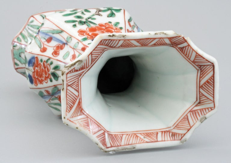 A scarce Chinese Kangxi porcelain octagonal yen yen vase decorated with vases containing floral arrangements in the Famille Verte palette and dating between 1662 and 1722. The vase is hand painted to each of the six sides with a simple red painted