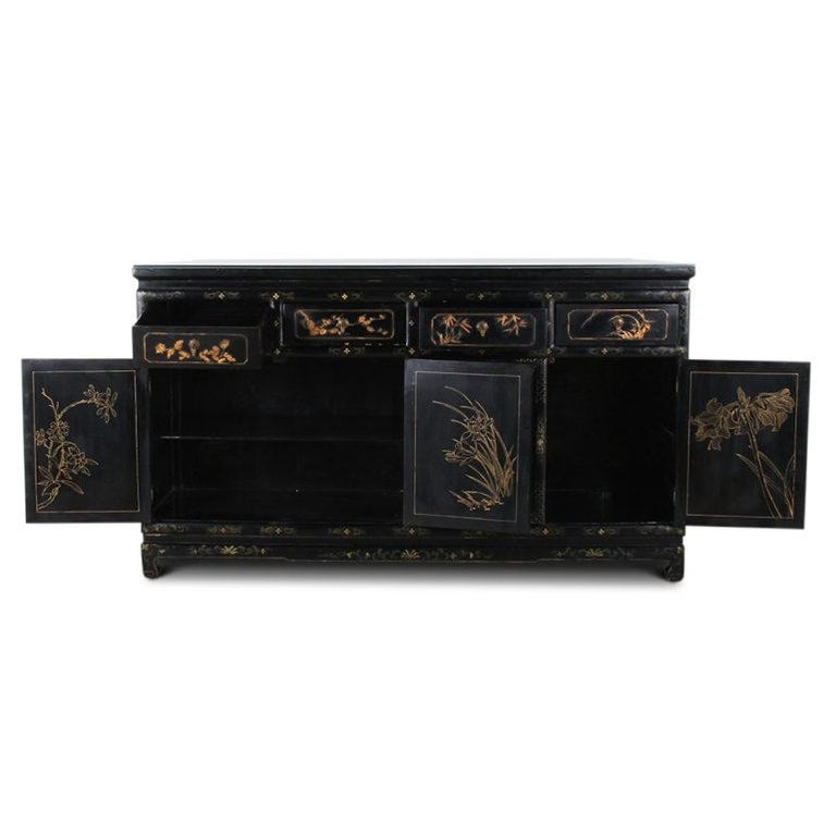 A vintage Chinese sideboard, or cabinet, with four drawers over four cabinets, the black lacquered case decorated with painted and applied decoration depicting flowers, birds, etc, circa 1950.