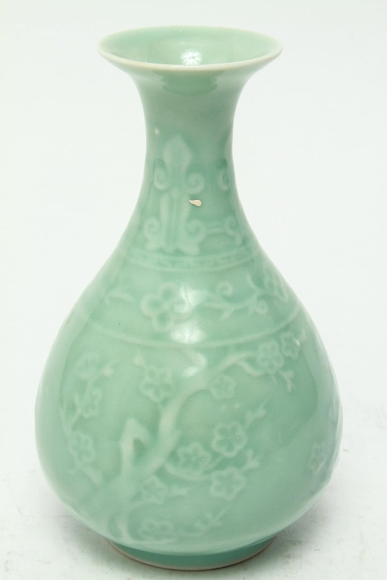 Chinese Longquan celadon-glazed Yuhuchunping bottle shaped vase with a globular body carved with blossoming branches. The underside has a green