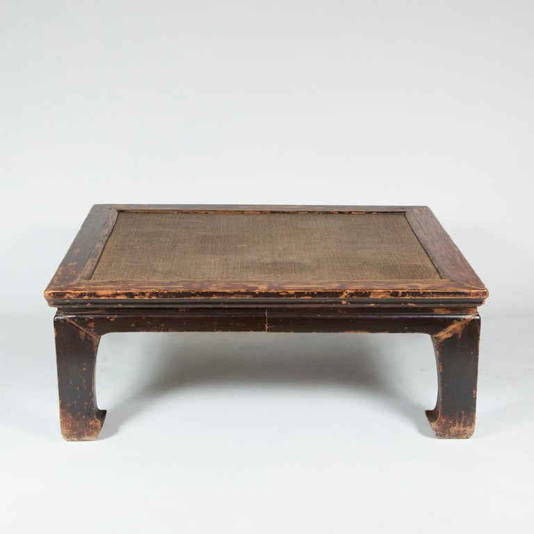 A Chinese painted elm low table with woven rattan inset top and hoof legs.