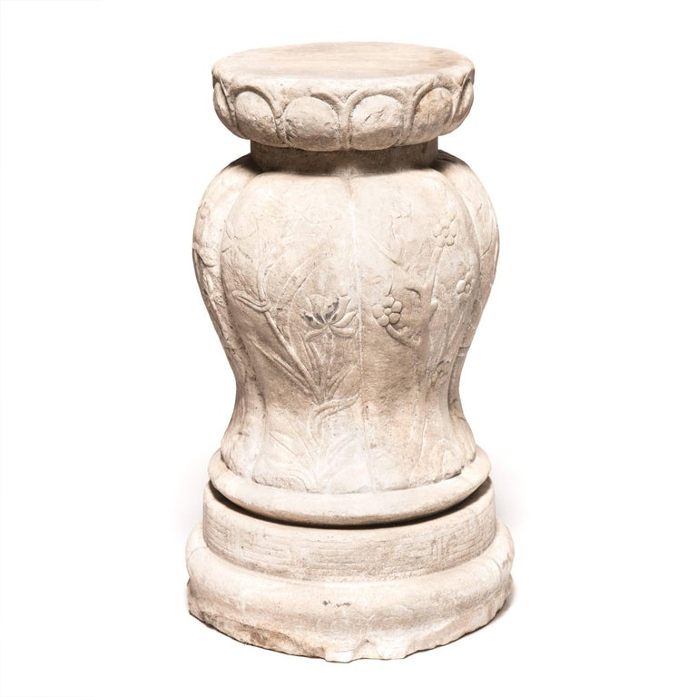 This finely carved marble pedestal is ideal for display inside or out. The raised pleats stand in for a melon's ribs and flow down from the pedestal top to the stepped disc base. The dynamic relationship from rounded top, to swelling centre, to
