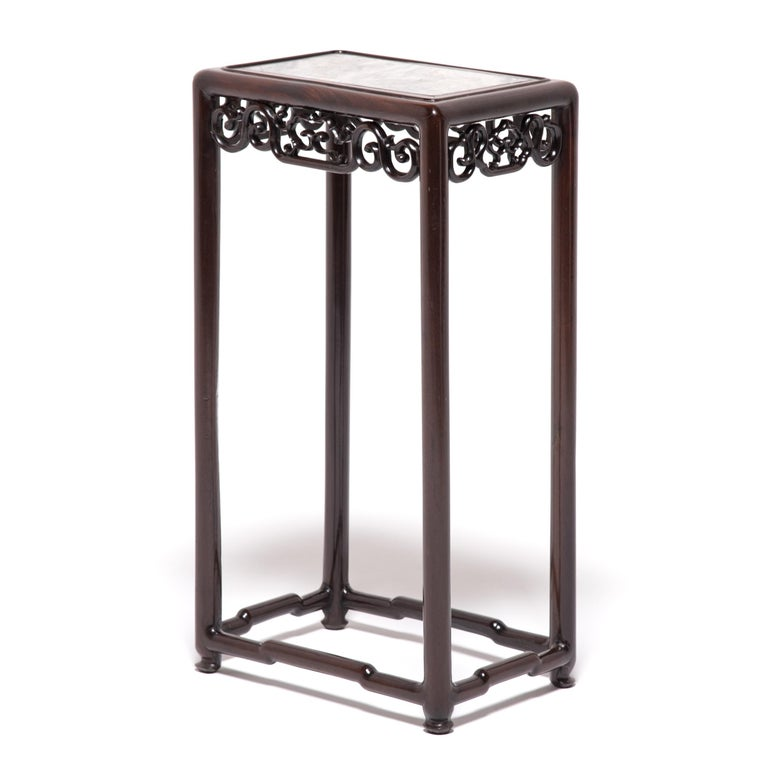 This elegant blackwood stand topped with marble was made in the bustling city of Shanghai during the Art Deco period. A product of the era, the table has an eclectic style of design that combines traditional craft motifs with bold, rich colors and