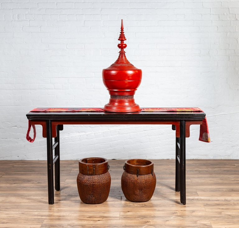 A Chinese Ming Dynasty style black lacquered altar console table from the early 20th century, with red accents. Charming us with is clean, simple lines and contrasting colors, this Chinese Ming style altar console table features a rectangular top