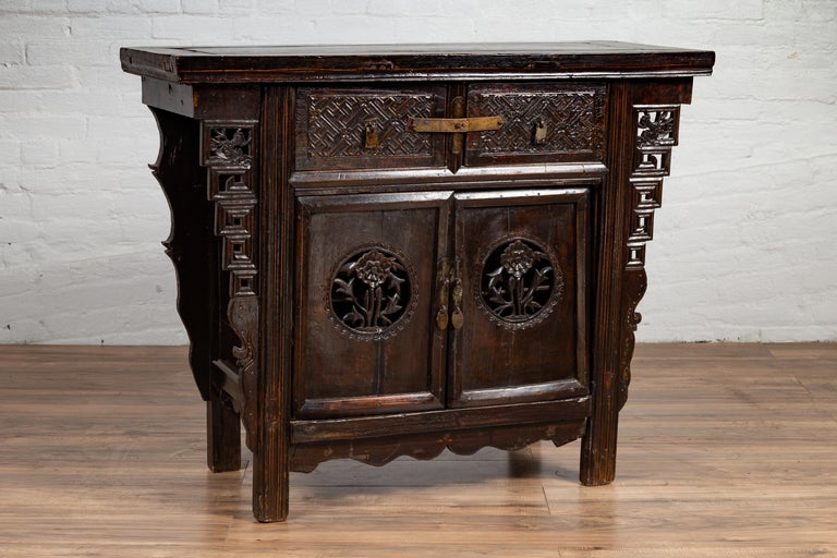 A Chinese Ming Dynasty style wooden butterfly cabinet from the 19th century, with carved spandrels, drawers, doors and dark patina. Born in China during the 19th century, this exquisite coffer called a butterfly cabinet, features a rectangular