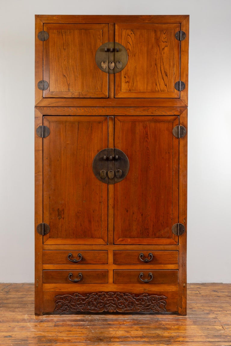 A Chinese Ming dynasty style two-section compound wedding wardrobe, with carved floral skirt, two sets of double doors, lower drawers and brass hardware. Born in China during the early years of the 20th century, this large compound wardrobe features