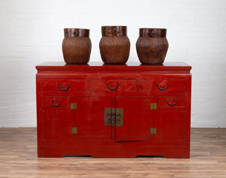 An antique Chinese Ming Dynasty style red lacquered console cabinet from the early 20th century, with five drawers and double doors. Born in China during the early years of the 20th century, this console cabinet captures our attention with its red