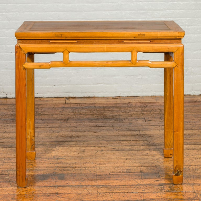 A Chinese Ming Dynasty style vintage waisted altar console table from the mid-20th century, with horsehoof legs and humpbacked stretcher. Created in China during the midcentury period, this Ming style altar table features a rectangular waisted top