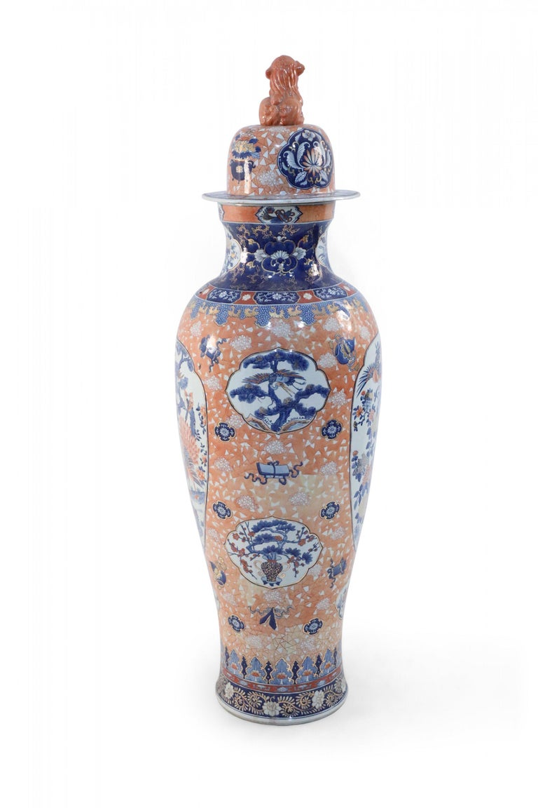 Chinese monumental, lidded porcelain urn celebrating Japanese Imari ware in both palette and design, featuring natural scenes of birds and flowering trees set against a light-orange, geometric-patterned background, and topped with a foo dog-finial
