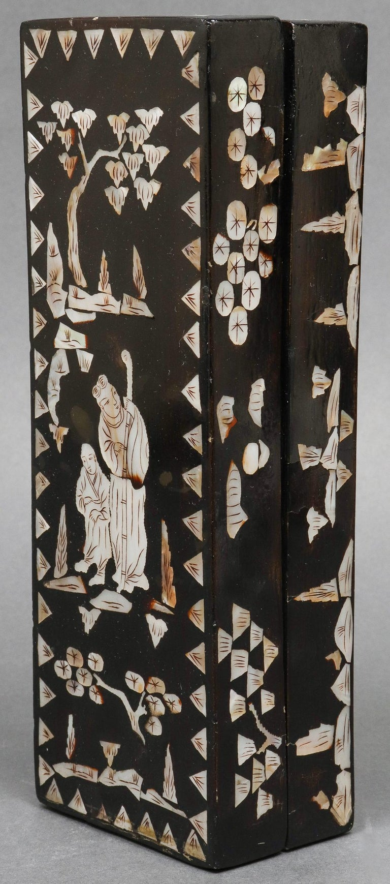 Chinese mother of pearl inlaid lacquered long rectangular box, the cover depicting two figures or immortals with all-over landscape decoration, circa late 19th-early 20th century. 2.5