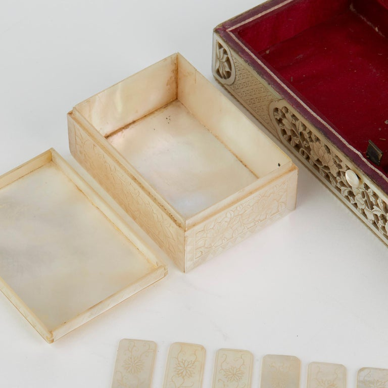 An exceptional and rare Chinese mother of pearl mounted games box with four matching interior boxes containing gaming counters and dating from the 18th century. The rectangular shaped box has a hinged cover, the wooden body mounted with deep carved