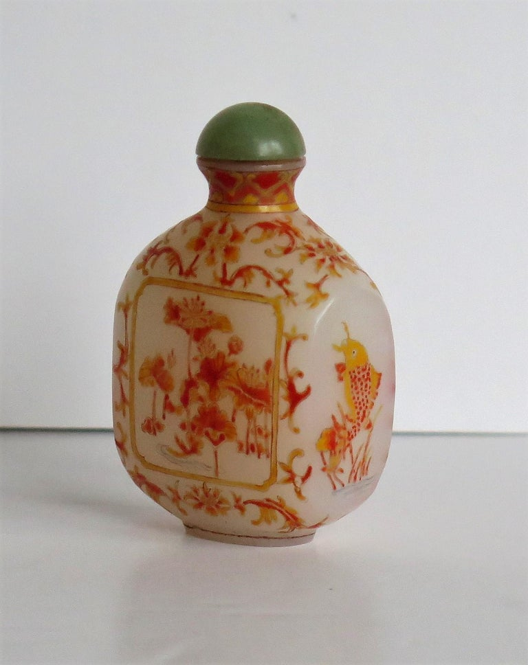 This is a very good Chinese glass snuff bottle, beautifully hand enameled, which we date to the earlier part of the 20th century, circa 1920 or possibly earlier  It is made of a milky white opaque glass and sits on a low oval foot. The bottle has