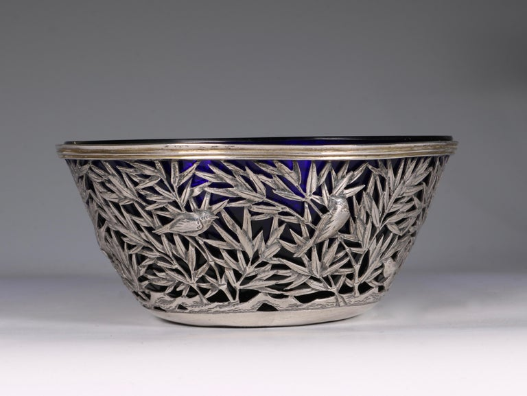 An Open-work Silver Bowl. With a pierced design of birds both flying and perched among bamboo issuing from rockwork. The details are finely incised. Together with the heavy blue glass liner. 