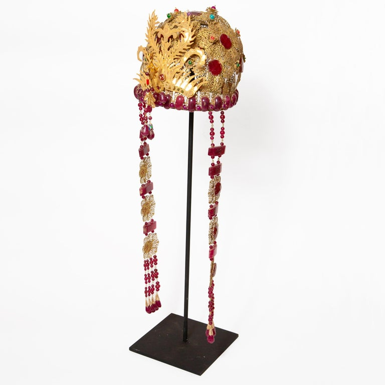 Chinese opera theatre headdress, ruby stone. Chinese opera theatre headdress with ornate gold flowers, dangling tassels, and rooster. Mid-20th century, mounted on a custom black painted metal base. Size: 25