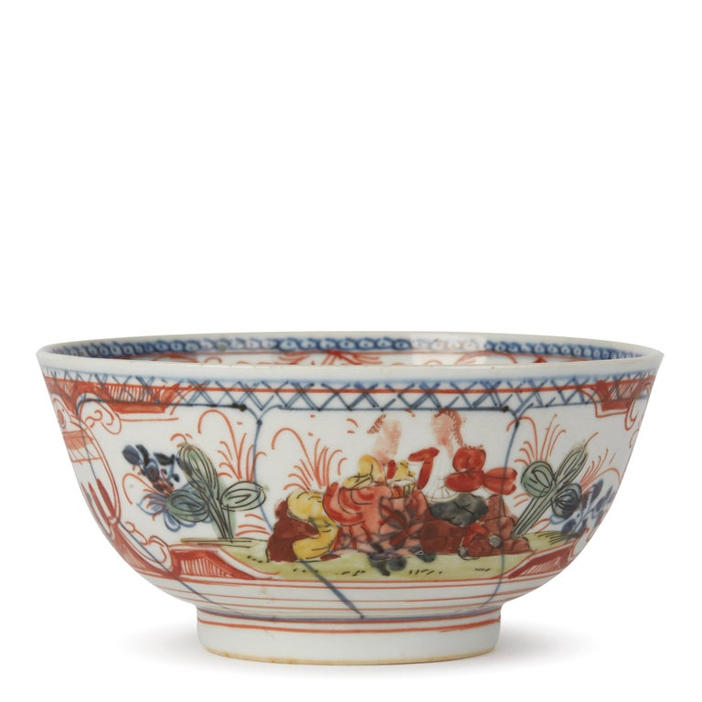 An unusual antique Chinese early Qianlong, or earlier, porcelain bowl, probably Dutch decorated with underglaze blue panels containing floral designs and over painted with seated figures on rockwork and with a figure on a ladder picking fruit
