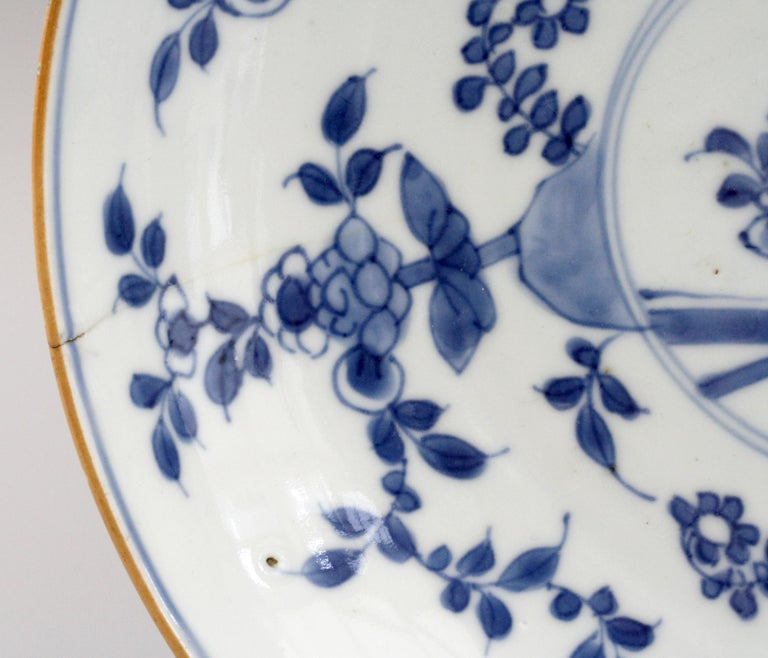 A finely made pair Chinese Kangxi blue and white floral decorated porcelain plates. The plates are of shallow bowl form with flowering roses around the inside of the dish around a small central panel containing a fence and further floral designs.