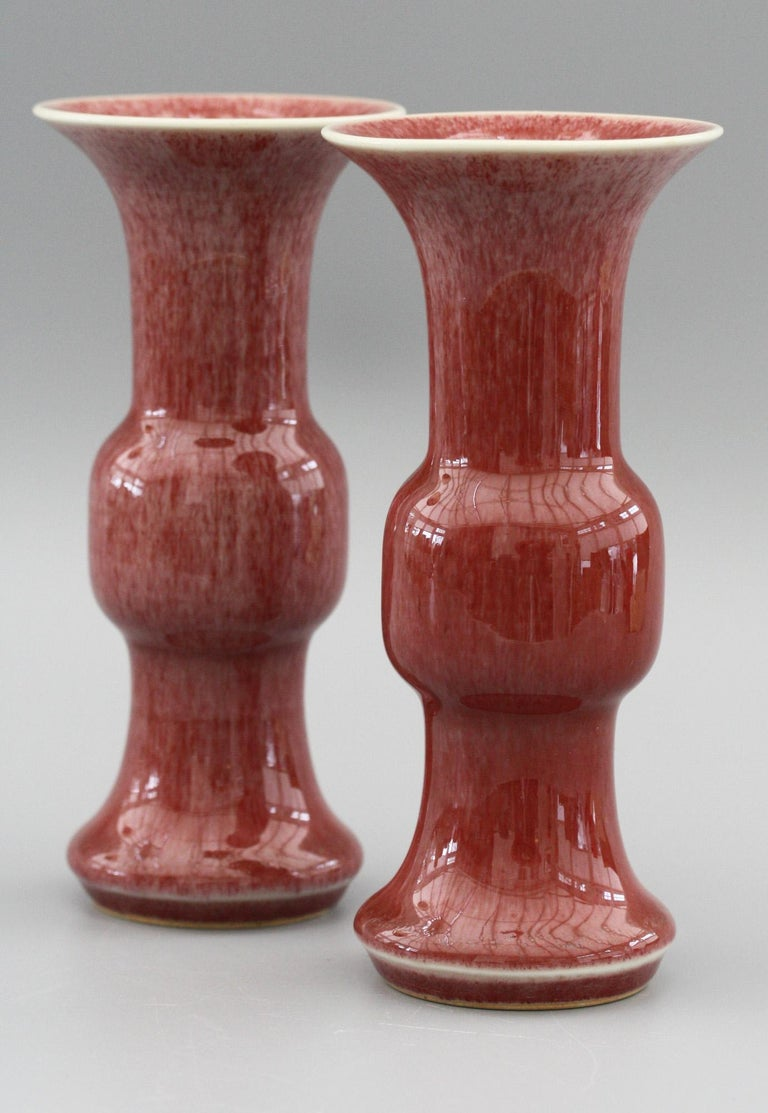 A fine and decorative pair Chinese Qianlong marked gu shaped porcelain vases decorated in red sang de boeuf glazes dating from the 20th century. The vases each have unglazed rounded feet with a skirted foot rim, a bulbous knop shaped body and