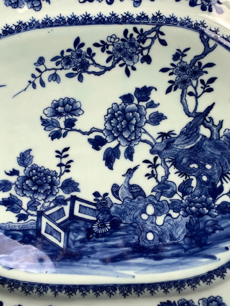 A Chinese blue and white porcelain platter hand-painted in the Qianlong dynasty in the 18th century. We see a beautiful garden scene painted in deep cobalt blue with oversized peonies, a pair of songbirds, and a second pair of birds flying above.