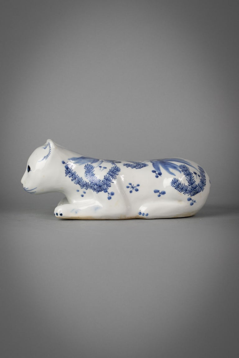 Chinese porcelain blue and white recumbent cat with underglaze blue fish as decoration.