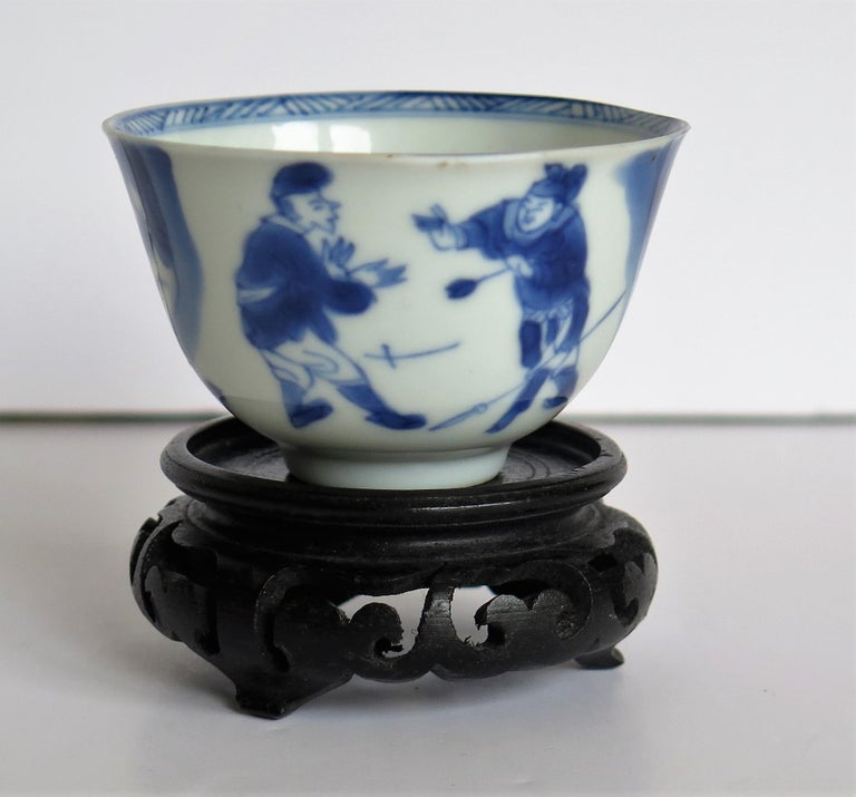 This is a beautifully hand painted Chinese porcelain blue and white Tea Bowl from the Qing, Kangxi period, 1662-1722, with a hand carved hard-wood Stand .  The tea bowl is very finely potted with a carefully cut base rim and a lovely rich glassy