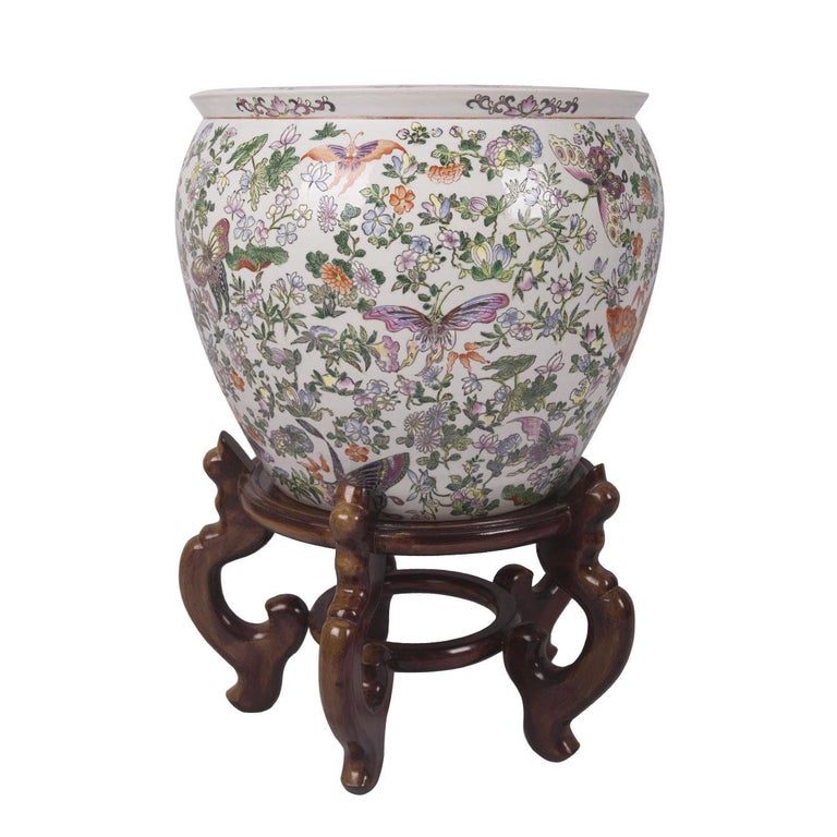 These colorful matching fishbowls were created in Hong Kong, China around 1960. Both fish bowls are round in shape, these porcelain bowls features beautiful hand painted butterflies and flowers throughout the exterior of these large fish bowls. The