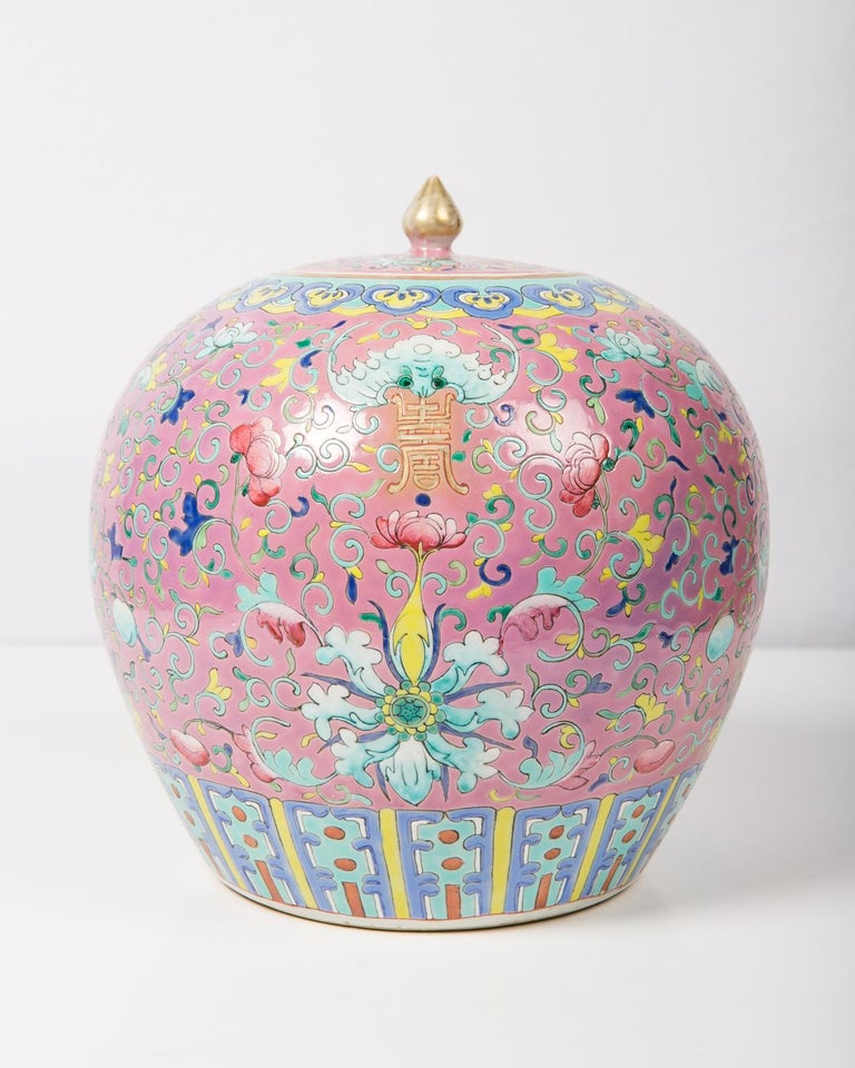 A Chinese porcelain ginger jar dating to the late Qing dynasty in the early 20th century. The ornate patterns are set against a soft pink background, a color scheme that became popular beginning in the Qianlong period. The jar is richly decorated in
