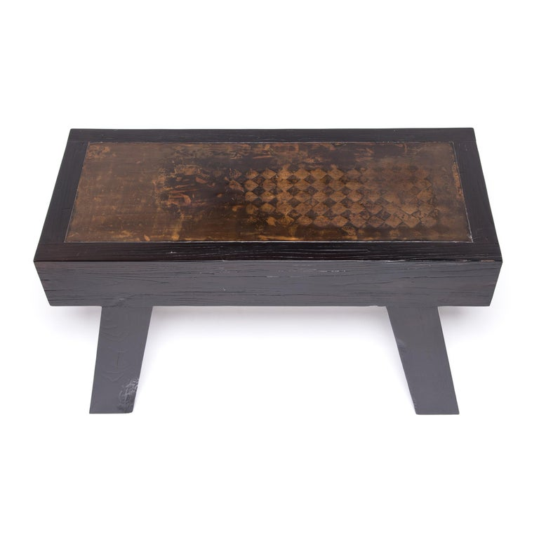 This charming contemporary table unites the organic appeal of natural wood with earthy ceramic. Blocky legs angle a thick tabletop inset with a weathered, diamond-patterned slab of earthenware. The combination weaves modern aesthetics with