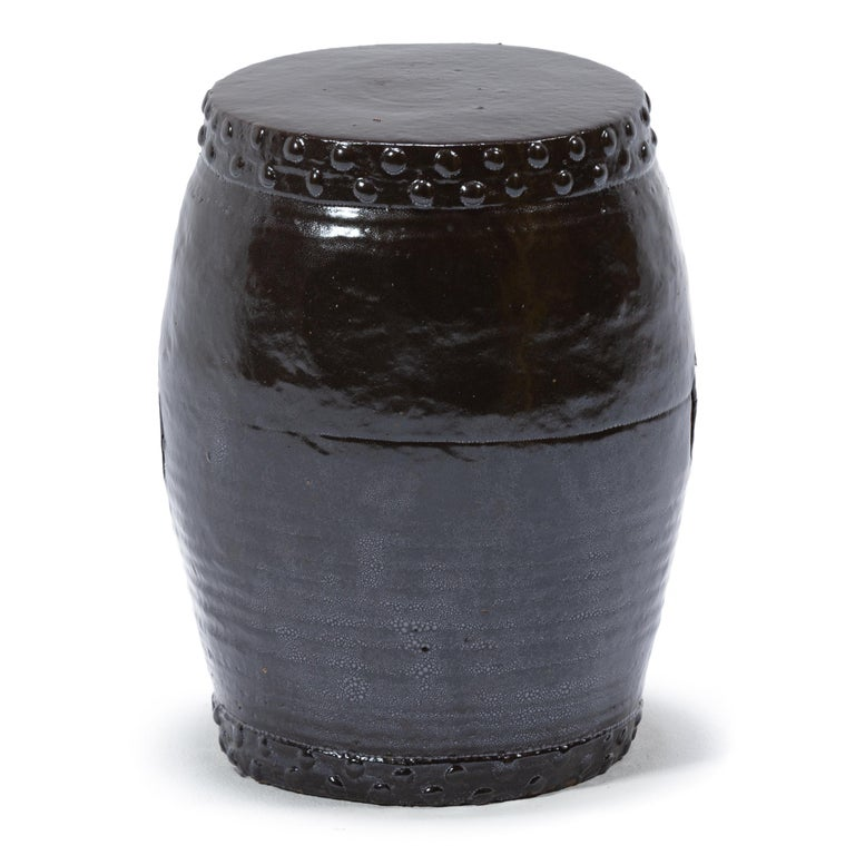 This early 20th century garden stool from China's Zhejiang province keeps with tradition with its simple drum-form shape, cloaked in a dark brown glaze. Ringing both the top and bottom, a pattern of boss-head nails imitates those used to stretch a