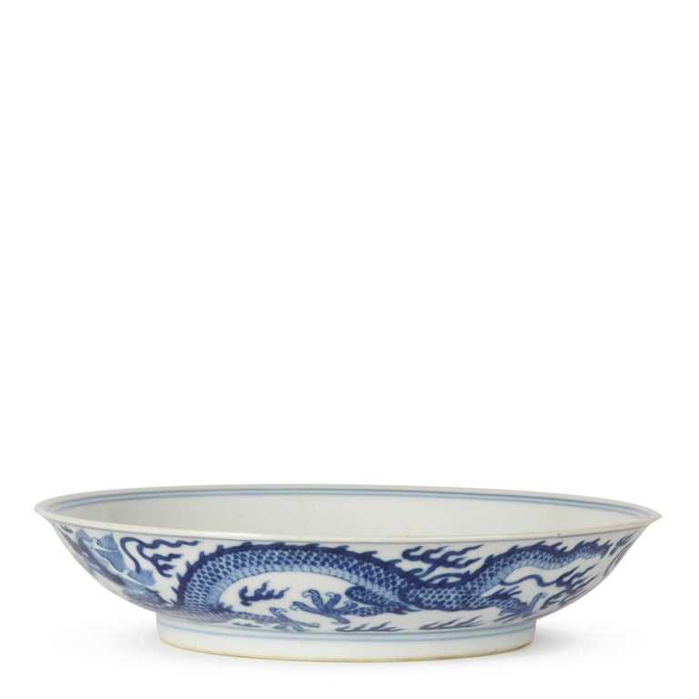 A stunning and rare Chinese Qianlong porcelain blue and white shallow dish finely decorated with a central five claw imperial dragon chasing a flaming pearl through clouds. The pattern is repeated around the outside rim of the dish with simple line